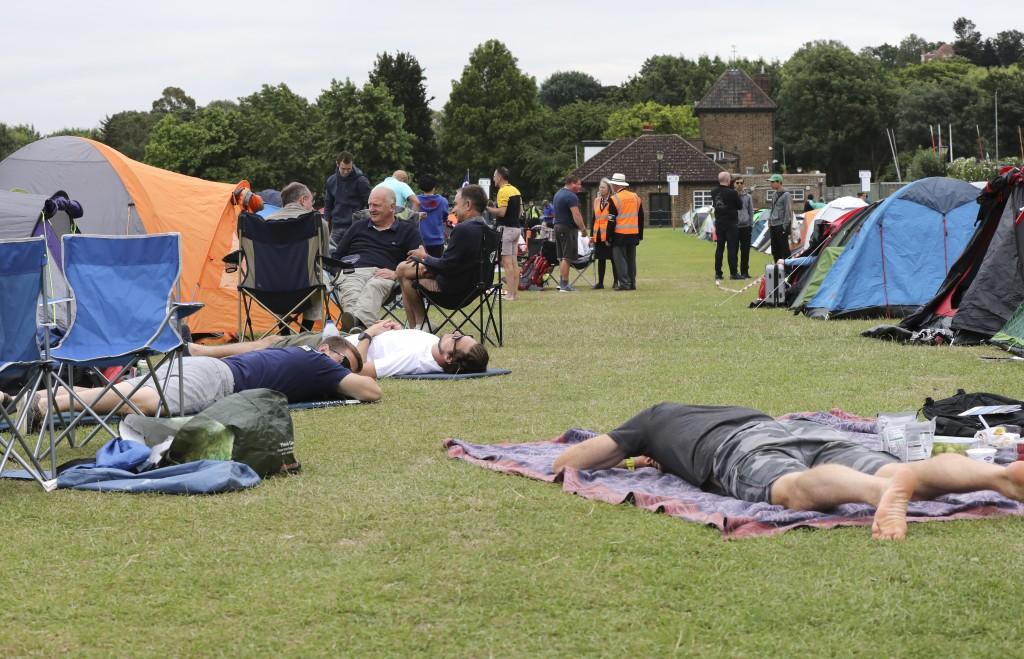 In this Tuesday, July 9, 2019, tennis fans rest as they wait in line for tickets to enter the Wimbledon Tennis Championships in London. For many the W
