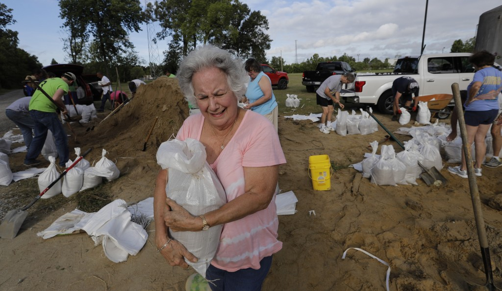 Diana Moreno carries a sandbag to her vehicle Friday, July 12, 2019, in Baton Rouge, La., ahead of Tropical Storm Barry.  The National Weather Service