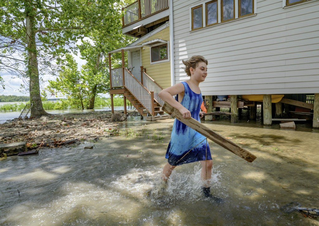 Tallulah Campbell, 8, clears out driftwood and other debris in preparation of Tropical Storm Barry near New Orleans, La., Thursday, July 11, 2019. The
