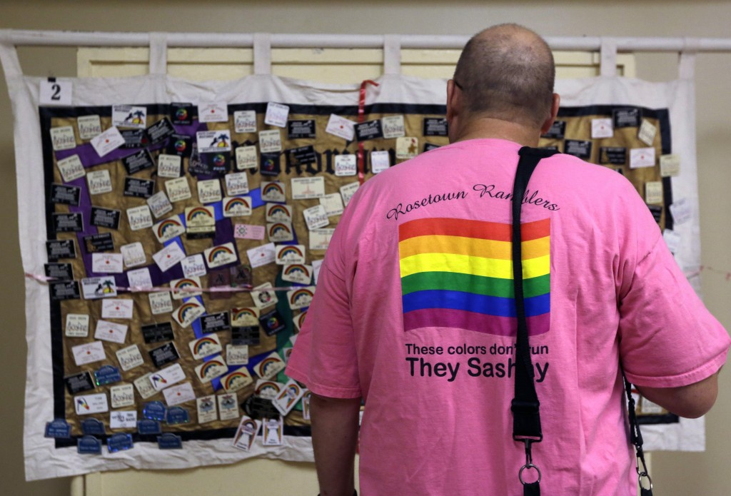 This July 4, 2019 photo shows a man viewing a memorial panel during the International Association of Gay Square Dance Clubs  annual convention in Phil