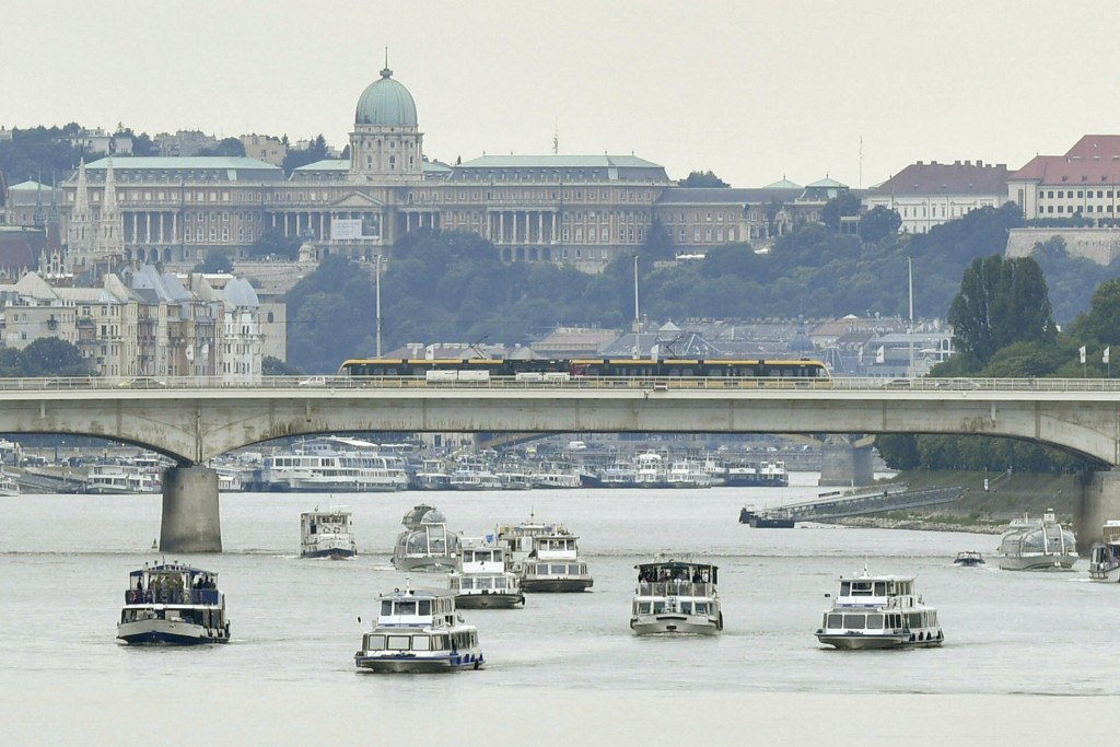 Backdropped by the Royal Castle on the top of Castle Hill a flotilla sails on River Danube during the funeral ceremony of the two Hungarian victims of