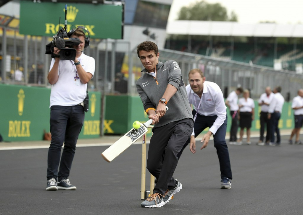 McLaren driver Lando Norris plays cricket on the track, during a preview day for the British Grand Prix at Silverstone racetrack, in Silverstone, Engl