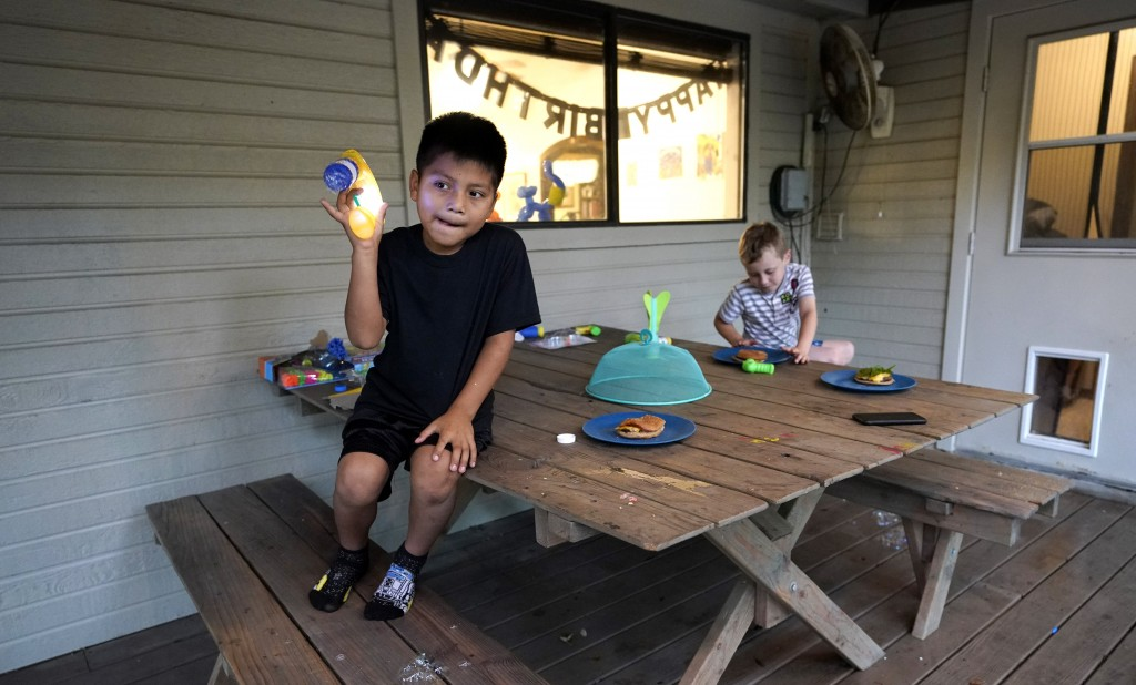 Byron Xol, left, an immigrant from Guatemala, plays with a bubble gun as he sits outside with Desmond Sewell Monday, June 24, 2019, in Buda, Texas. Af...