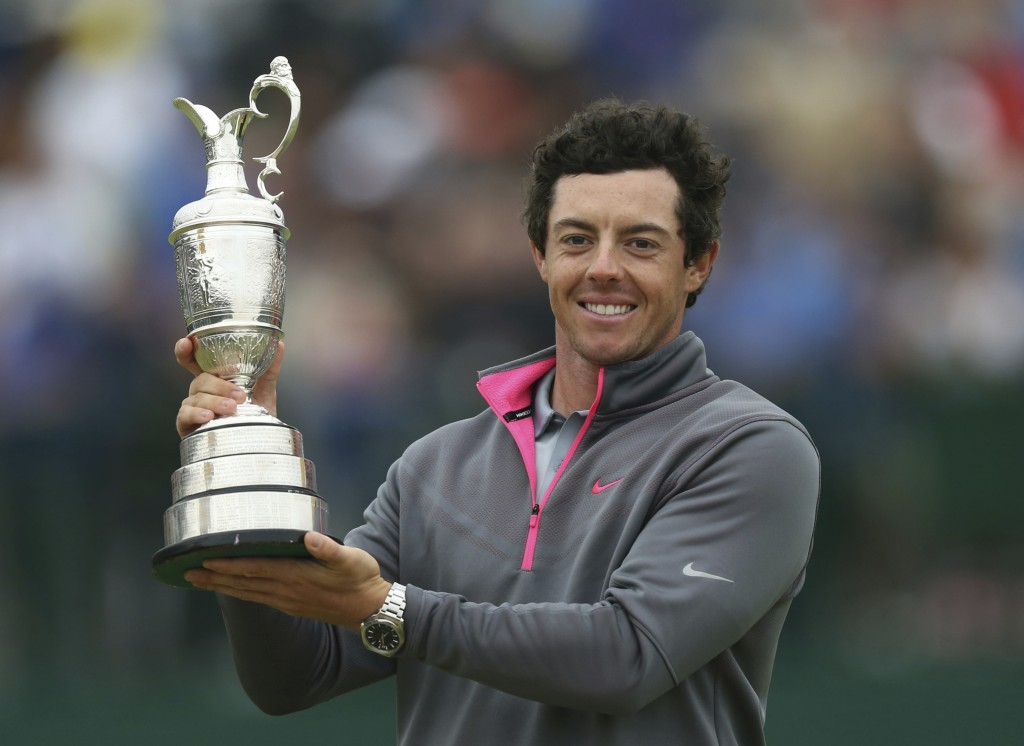 FILE - In this Sunday, July 20, 2014, file photo, Rory McIlroy of Northern Ireland holds up the Claret Jug trophy after winning the British Open Golf ...
