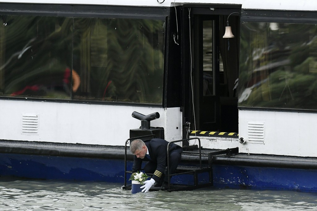 The urn containing the ashes of the sailor of the sunken boat is placed from a ship into River Danube by a ship's captain during the funeral ceremony