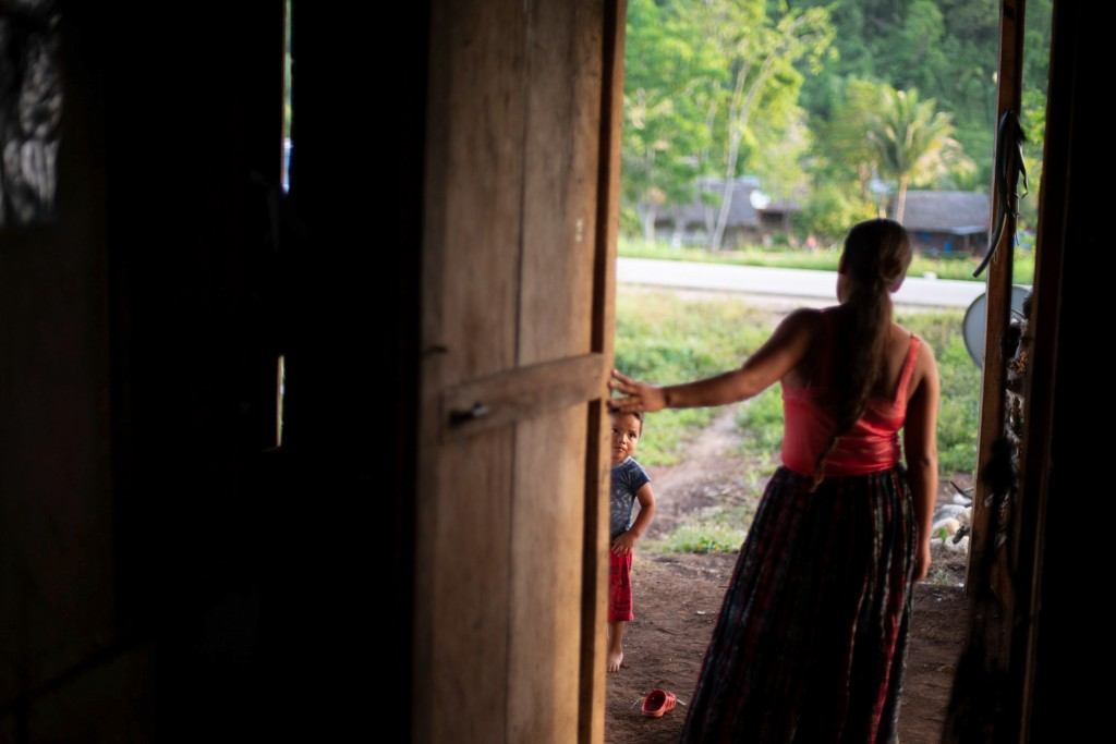 Florinda Xol, and her son, Alan, 3, stand at the door of their one-bedroom home in San Miguel El Limon, 475 kilometers (295 miles) away from Guatemala