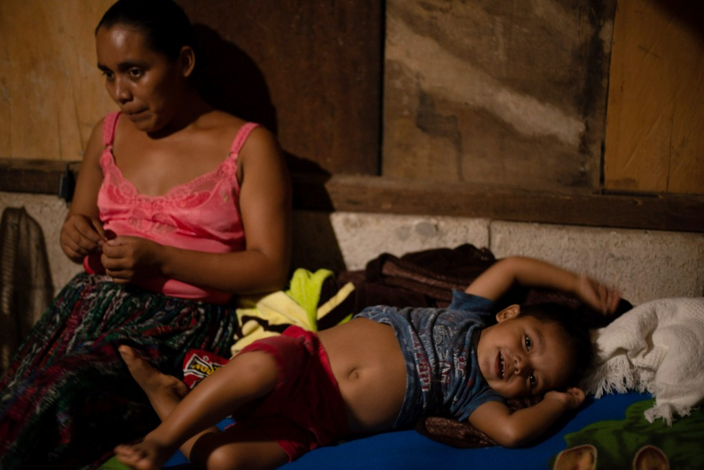 Florinda Xol , sits with one of her sons, Alan, 3, in their one-bedroom home in San Miguel El Limon, 475 kilometers (295 miles) away from Guatemala Ci...