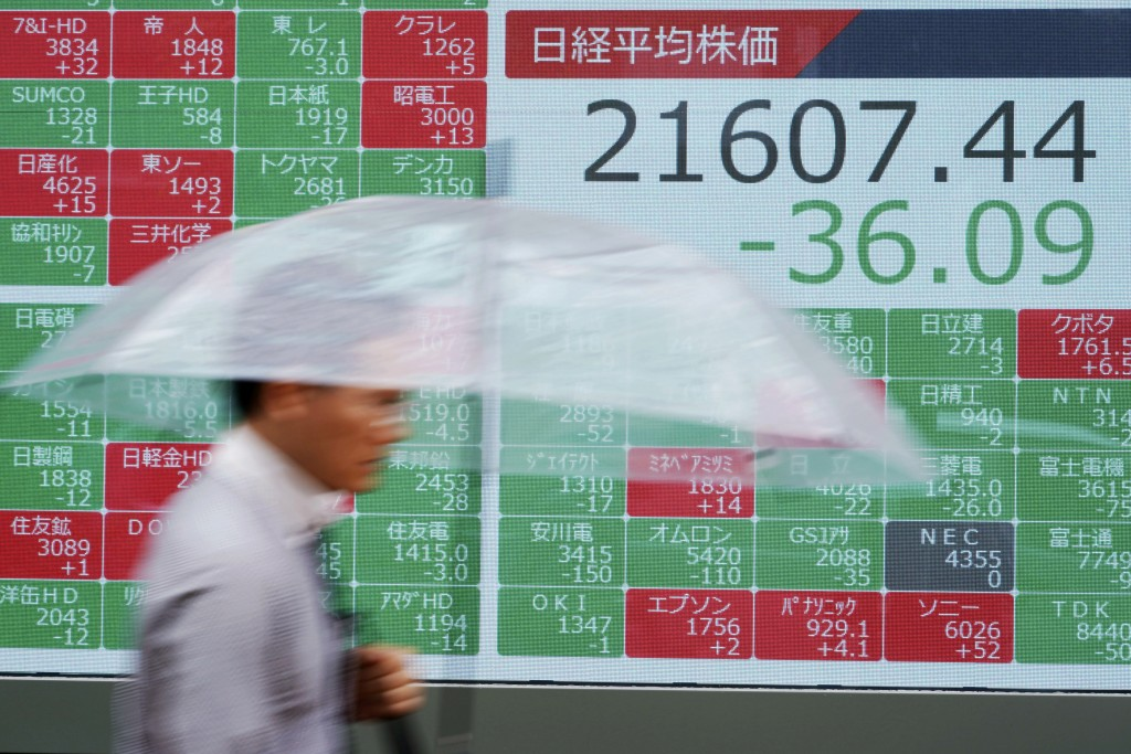 A man walks past an electronic stock board showing Japan's Nikkei 225 index at a securities firm in Tokyo Friday, July 12, 2019. Shares in Asia are mo...