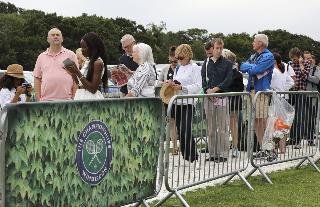 In this Tuesday, July 9, 2019 tennis fans wait in ...