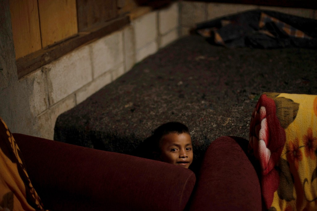 In this Sunday, June 23, 2019 photo, Cesar Xol, 7 years-old, plays on the house of his father David Xol in San Miguel El Limon, 475 kilometers (295 mi...