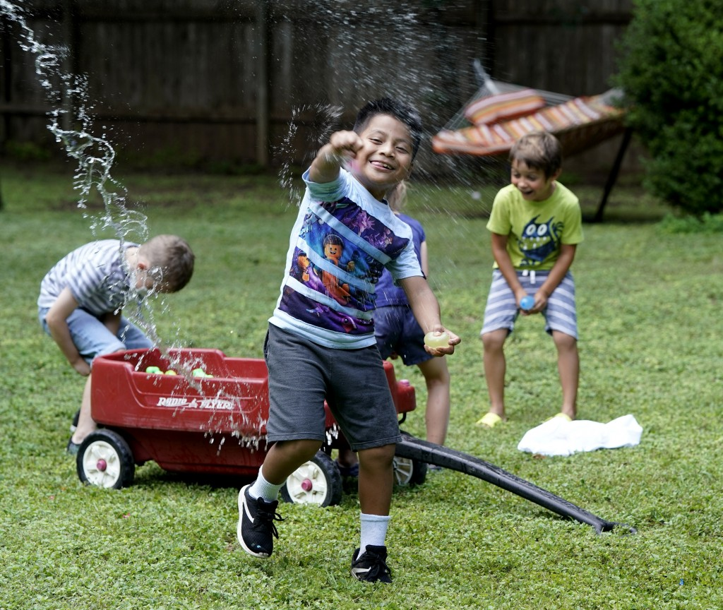 """Byron Xol, an immigrant from Guatemala, squeezes a water balloon during his birthday party Sunday, June 23, 2019, in Buda, Texas. """"Super good!"""" the 9-"""