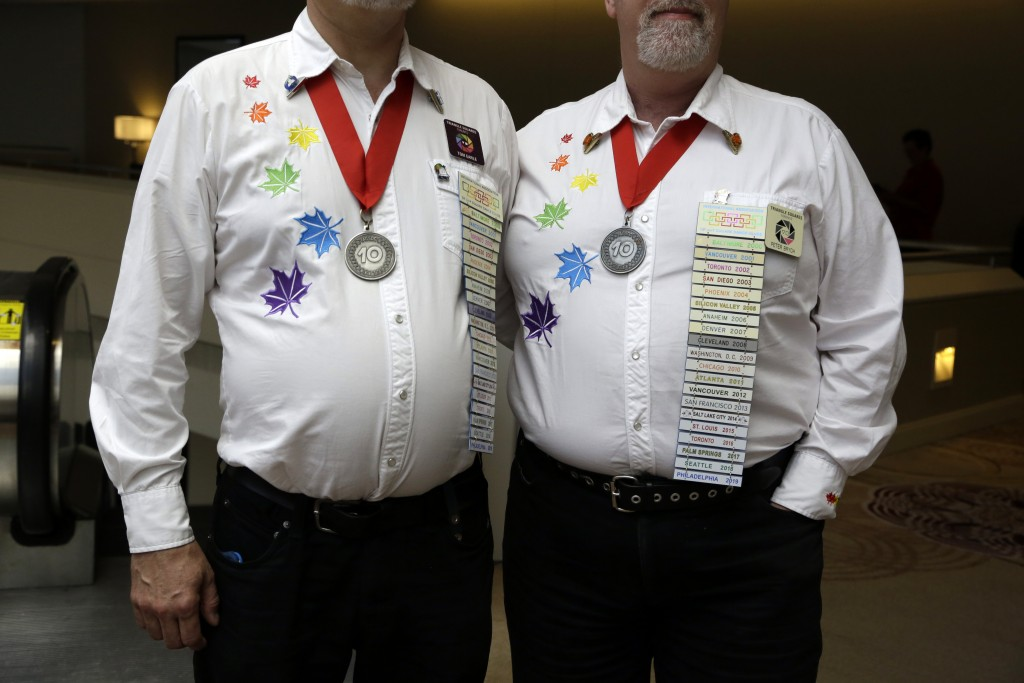 This July 4, 2019 photo shows Tom Earle, left, and Peter Brych, from the Triangle Squares club in Toronto, posing with their name badges and medallion