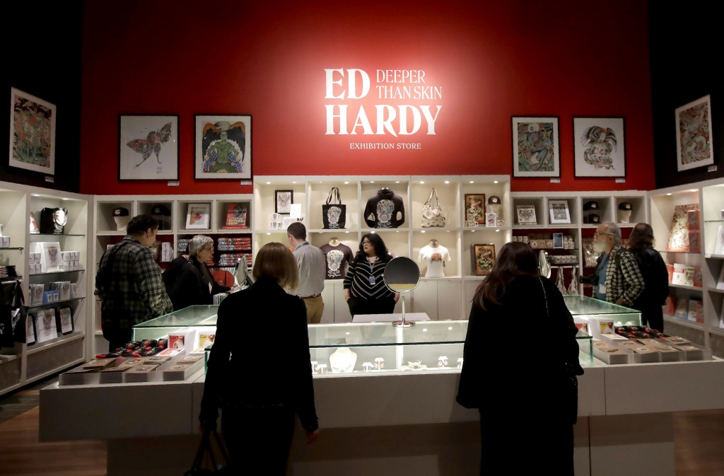 """In this Wednesday, July 10, 2019 photo, visitors look through merchandise for sale during a media preview of """"Ed Hardy: Deeper than Skin"""" at the de Yo..."""