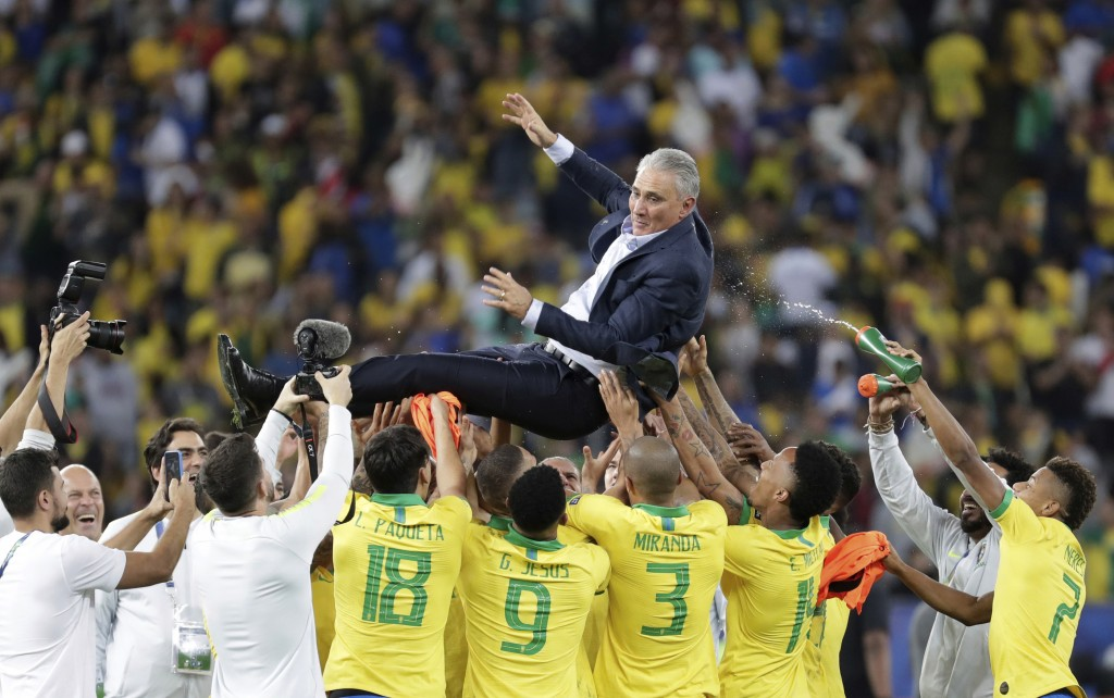 In this Sunday, July 7, 2019 photo, Brazil's coach Tite is thrown in the air by players to celebrate their 3-1 victory over Peru at the end of the fin
