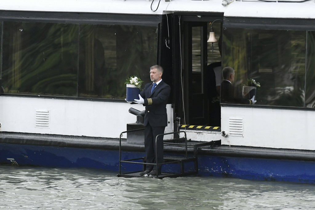 The urn containing the ashes of the sailor of the sunken boat is held by a ship's captain before he lowers it from a ship into River Danube during the
