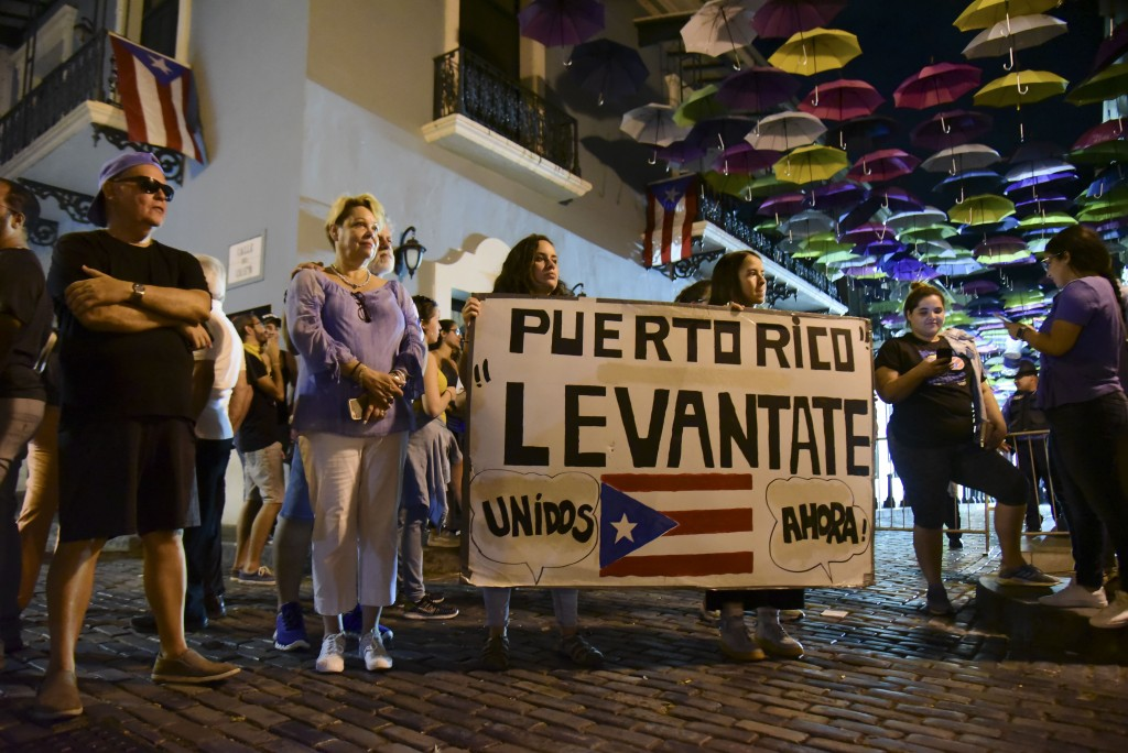 """Dozens of citizens holding a sign that reads in Spanish """"Puerto Rico rise up, unite now!"""" protest near the executive mansion denouncing a wave of arre"""