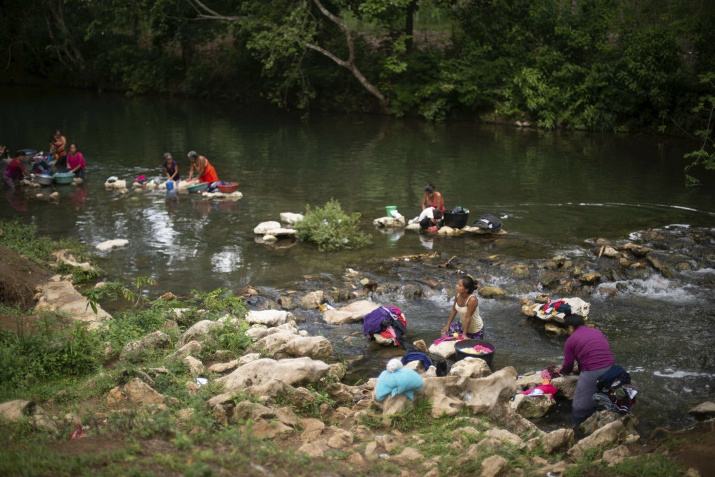 Women bathe and clean clothes in the river Limon, on Monday, June, 24, 2019, where David Xol often bathes and fishes, about 475 kilometers (295 miles)...