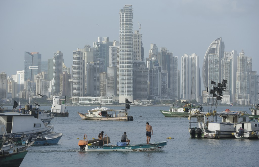 In this Thursday, July 4, 2019 photo, with the skyline of Panama City in the background, fishermen ride their boat on Panama City bay. The capital of