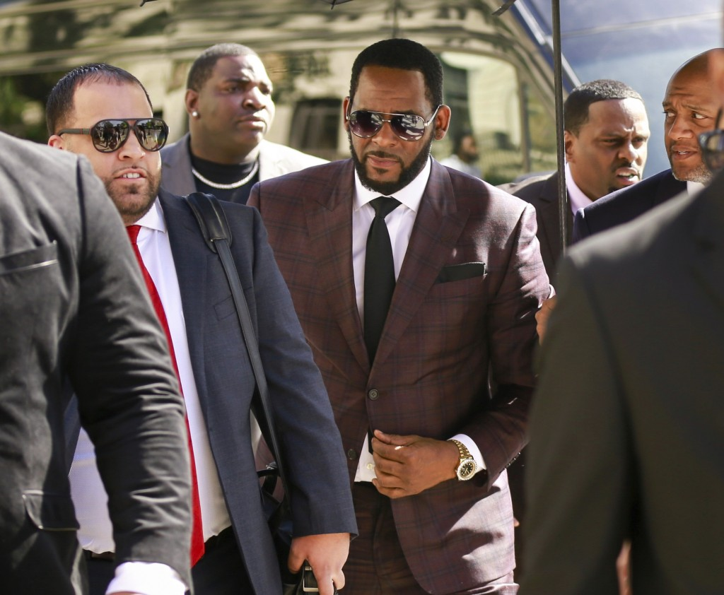 FILE - In this June 26, 2019, file photo, R&B singer R. Kelly, center, arrives at the Leighton Criminal Court building for an arraignment on sex-relat...