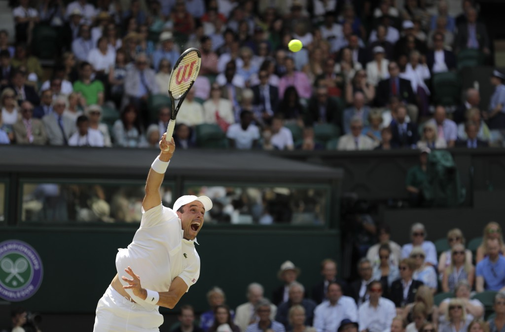 Spain's Roberto Bautista Agut serves to Serbia's Novak Djokovic during a men's singles semifinal match on day eleven of the Wimbledon Tennis Champions