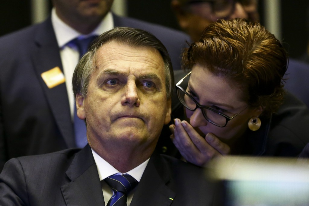 In this May 29, 2019 handout photo provided by Agencia Brasil, Brazil's President Jair Bolsonaro listens as Carla Zambelli whispers into his ear durin