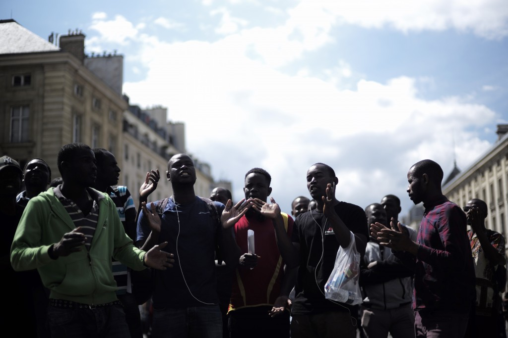 Migrants shout outside the Pantheon monument, where illustrious French figures are buried, in the Latin quarter of Paris, Friday, July 12, 2019. Dozen