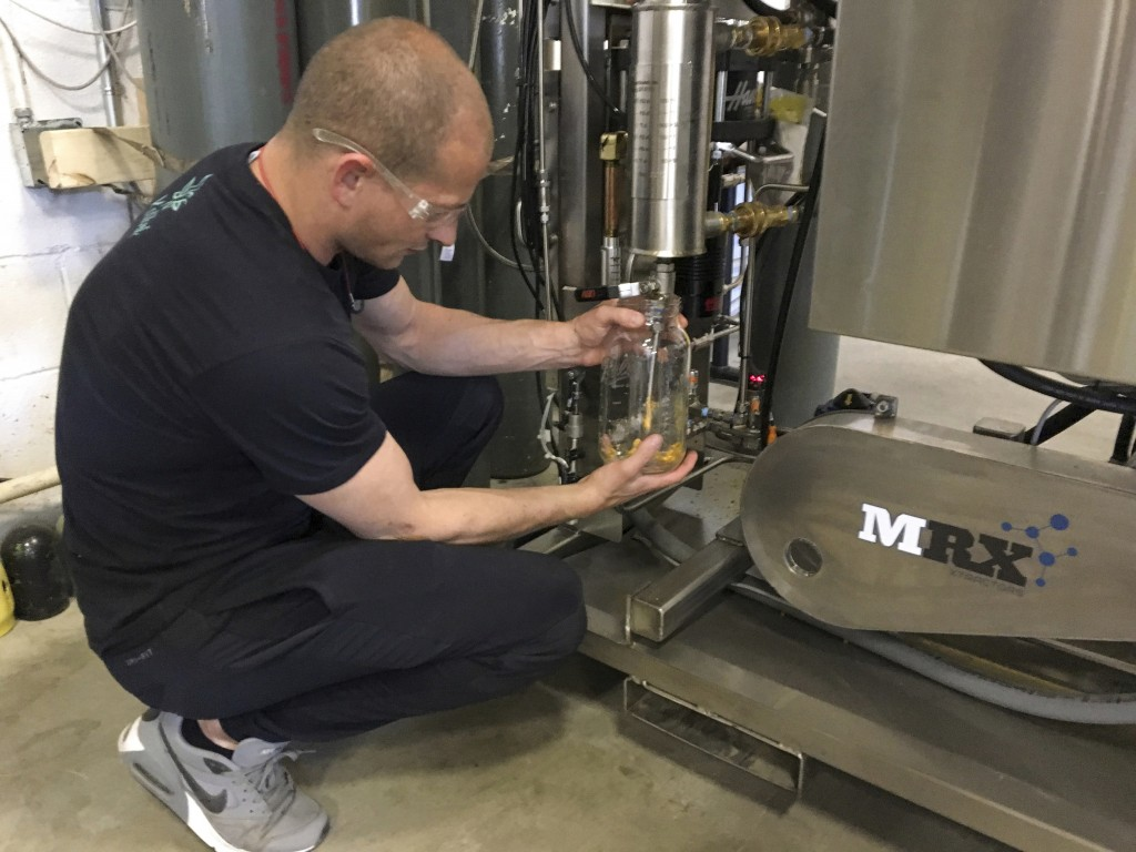 In this Tuesday, July 2, 2019 photo, Brent Steffensen, a hemp extractor at the processing facility Wasatch Extraction, uses a machine to extract fats,...