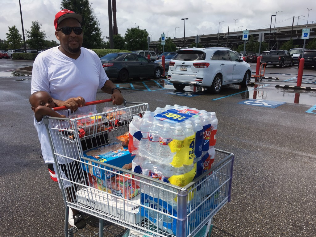 Terrence Watkins and his son Kang, 3, load up with water and other supplies in New Orleans, Friday, July 12, 2019, as Tropical Storm Barry threatens.