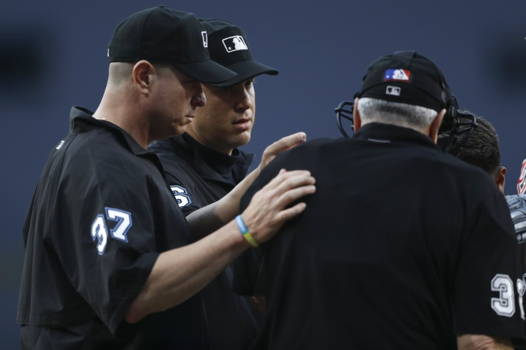 Second base umpire Chris Segal, second from left, and third base umpire Carlos Torres, left, talk with home plate umpire Dana DeMuth after DeMuth was