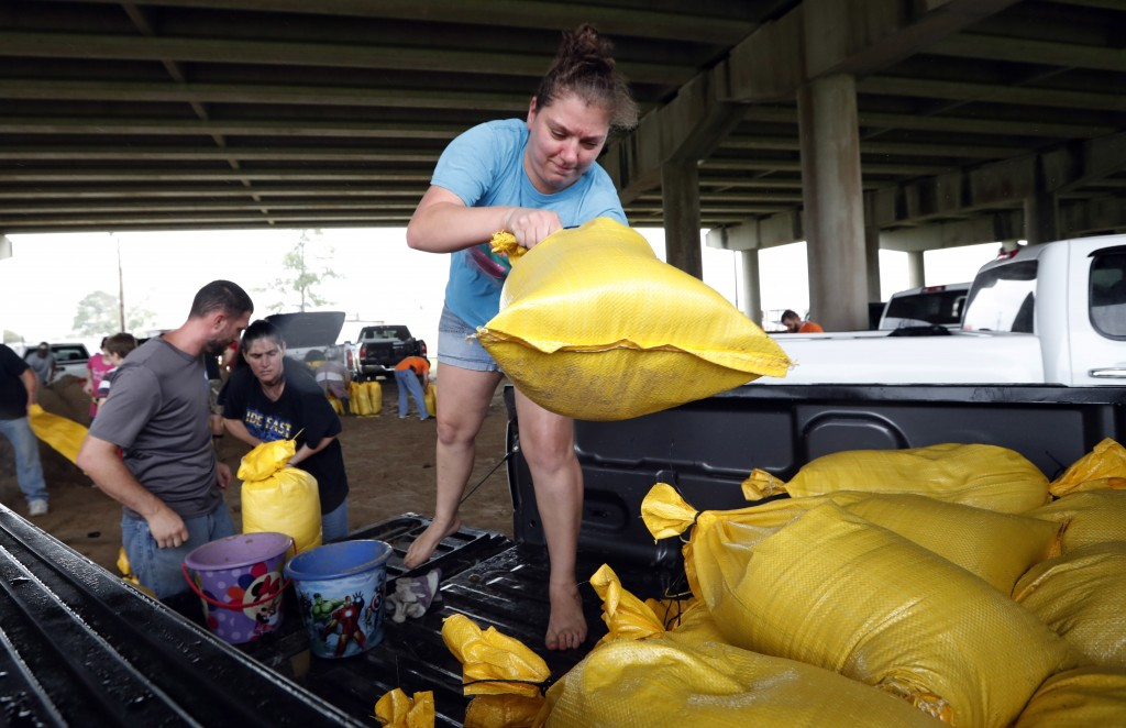 Tiffany Delee tosses a filled sandbag into the back of the family truck, while her husband Mike Delee, left, readies to tie up another bag, in Morgan