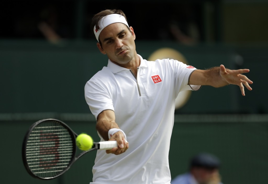 Switzerland's Roger Federer returns the ball to Spain's Rafael Nadal during a men's singles semifinal match on day eleven of the Wimbledon Tennis Cham