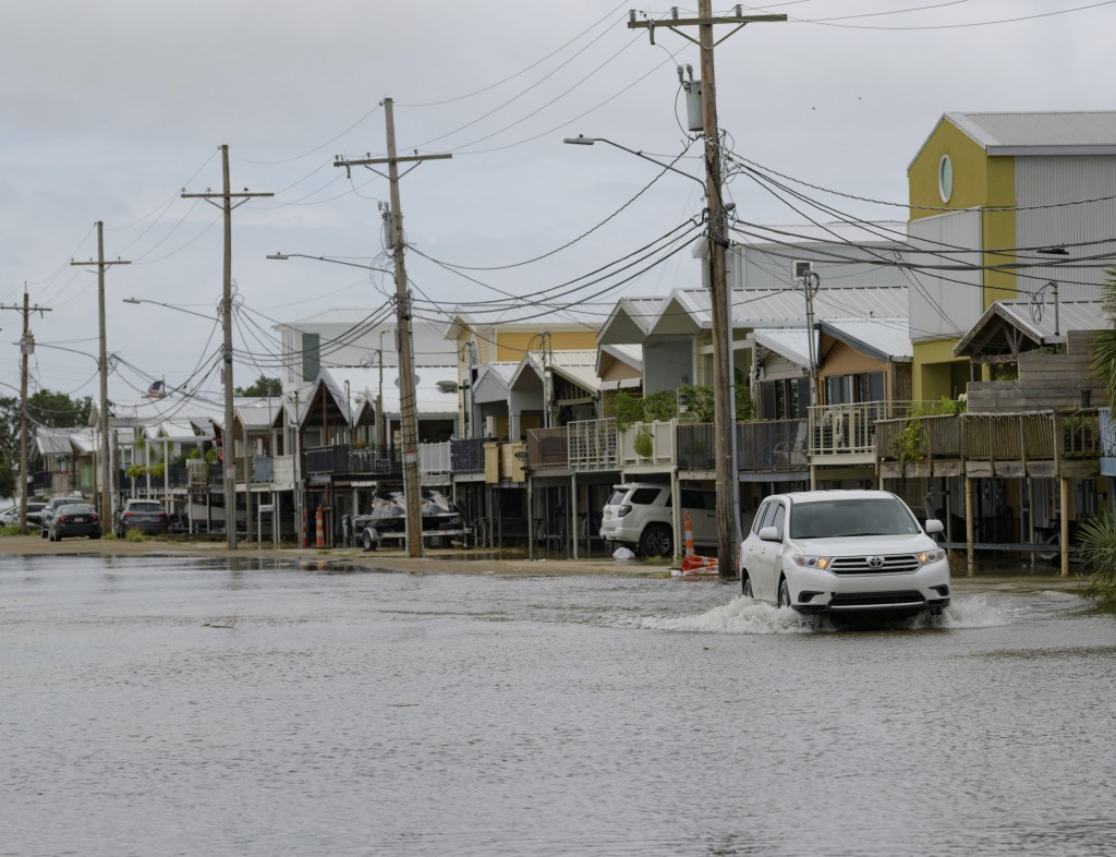 An SUV travels down Breakwater Drive in New Orleans, La., Friday, July 12, 2019, near the Orleans Marina as water moves in from Lake Pontchartrain fro