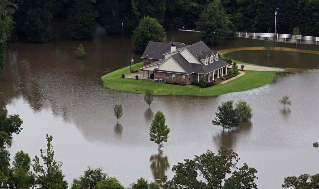 FILE- In this Aug.13, 2016 aerial photo over Amite, La., flooded homes are seen from heavy rains inundating the region. Memories of an epic flood that