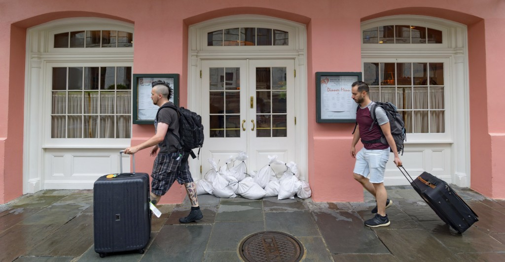 People walk past Brennan's restaurant in the French Quarter with sandbags on the front door as bands of rain from Tropical Storm Barry from the Gulf o