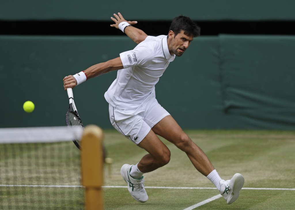 Serbia's Novak Djokovic returns to Spain's Roberto Bautista Agut in a Men's singles semifinal match on day eleven of the Wimbledon Tennis Championship...