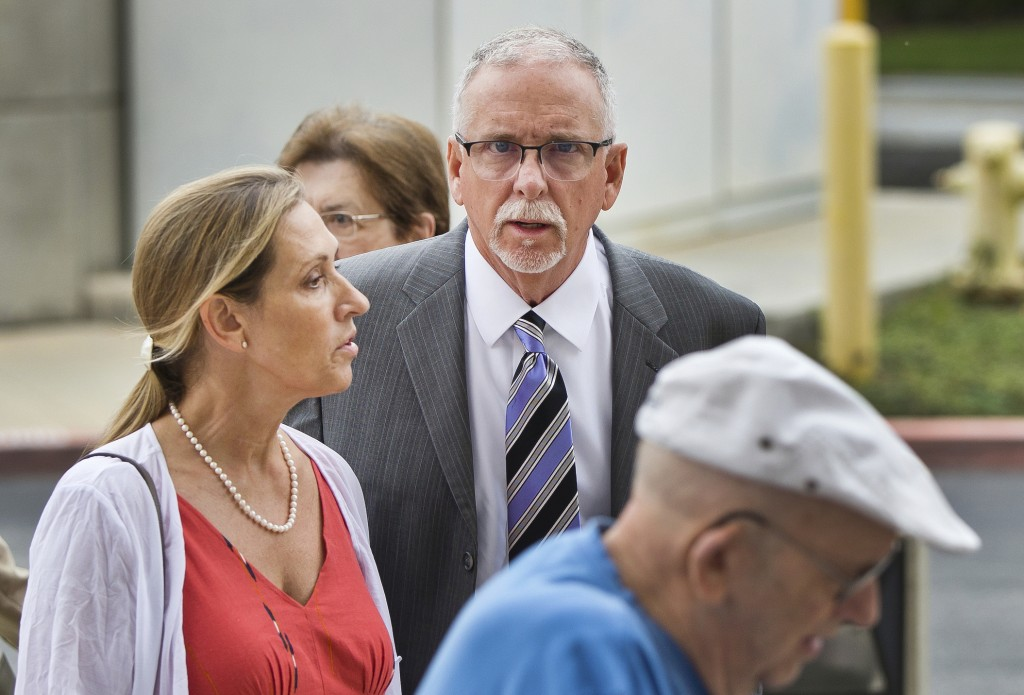 FILE - In this June 26, 2019 file photo UCLA gynecologist James Heaps, center, and his wife, Deborah Heaps, arrive at Los Angeles Superior Court. Nine