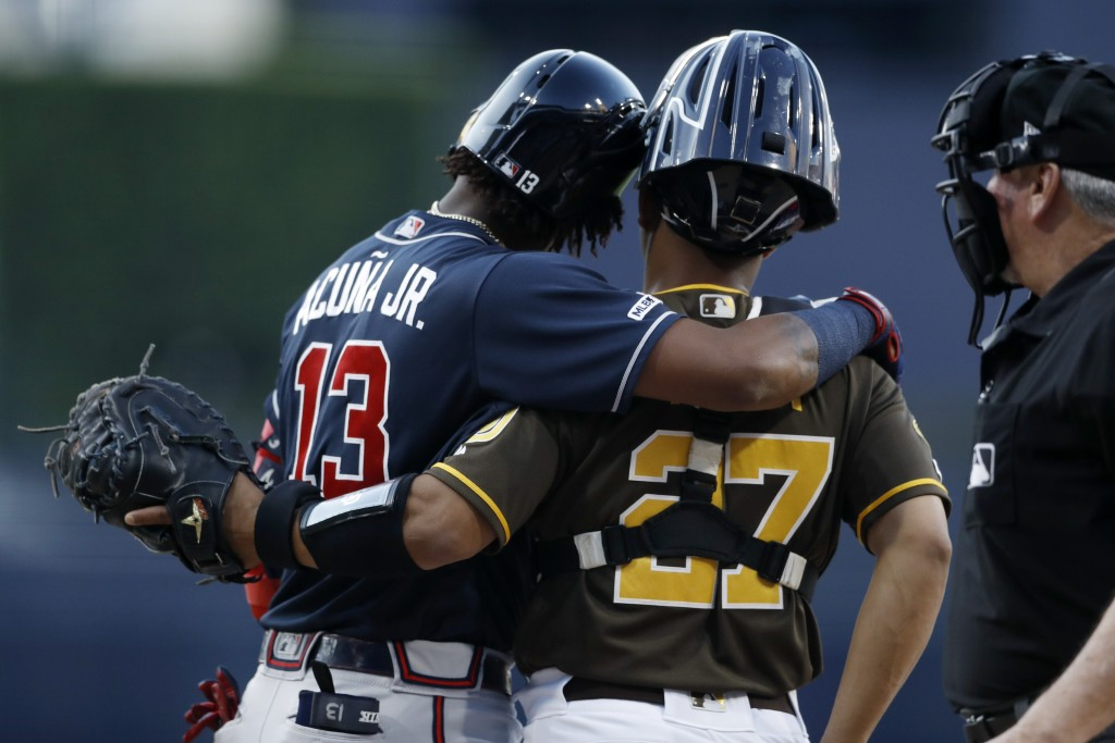 Atlanta Braves' Ronald Acuna Jr. (13) hugs San Diego Padres catcher Francisco Mejia (27) as he steps up to bat during the first inning of a baseball g