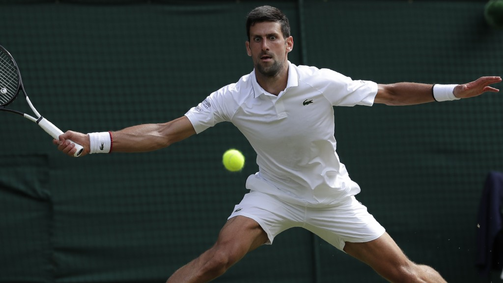 Serbia's Novak Djokovic returns the ball to Spain's Roberto Bautista Agut during a men's singles semifinal match on day eleven of the Wimbledon Tennis...