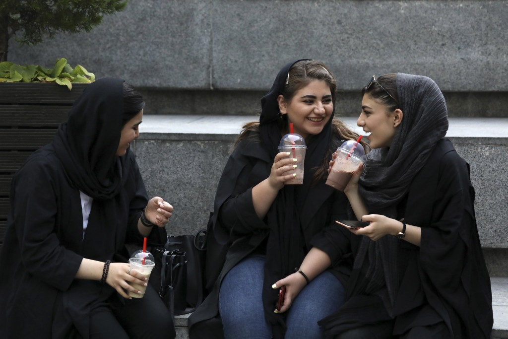 In this Tuesday, July 2, 2019 photo, youngsters spend an afternoon while siting on steps outside a shopping mall in northern Tehran, Iran.  A few dari