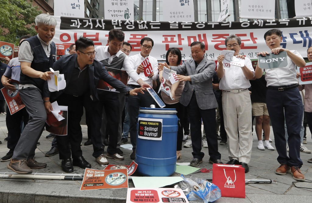 South Korean small and medium-sized business owners throw papers showing logos of major Japanese brands into a trash can during a rally calling for a