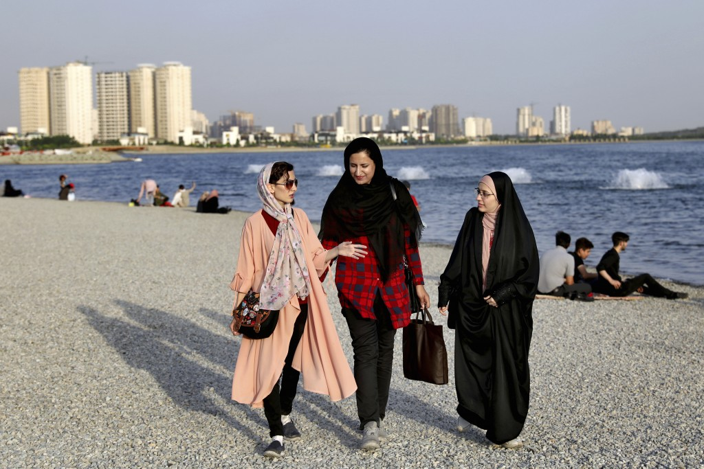 In this Saturday, July 6, 2019 photo, women walk on the shore of the Persian Gulf Martyrs' Lake in Tehran, Iran.  A few daring women in Iran's capital