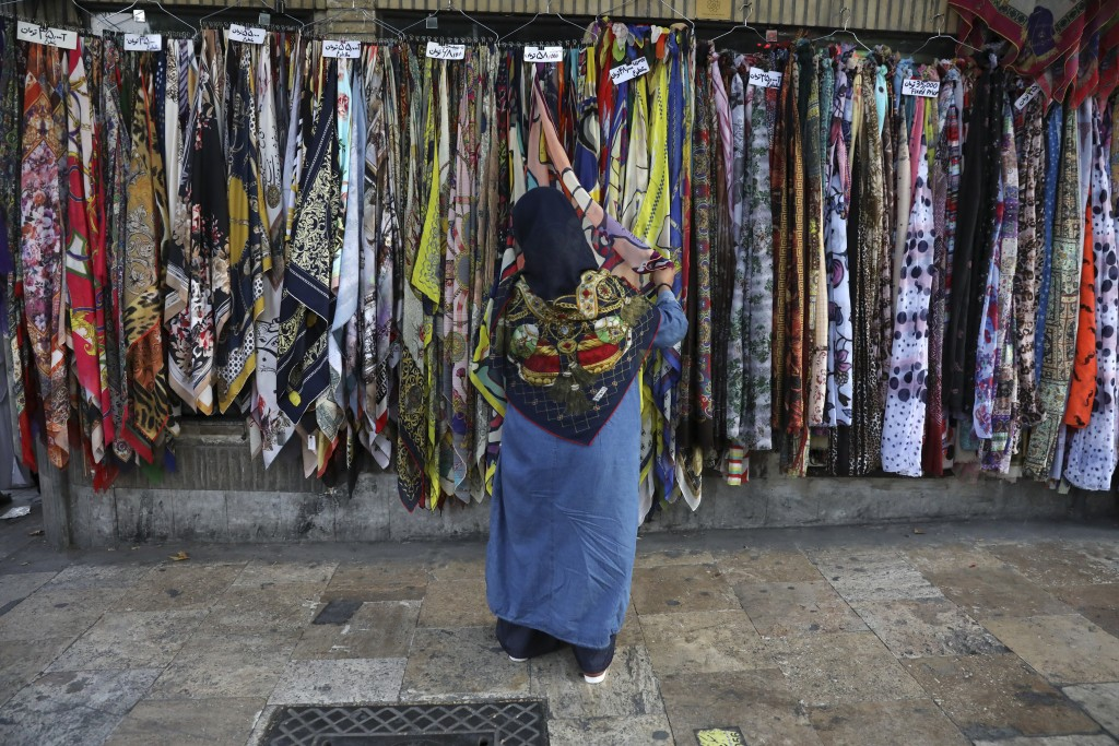 In this Tuesday, July 2, 2019 photo, an Iranian woman inspects headscarves of a vendor on a sidewalk in northern Tehran, Iran. A few daring women in I