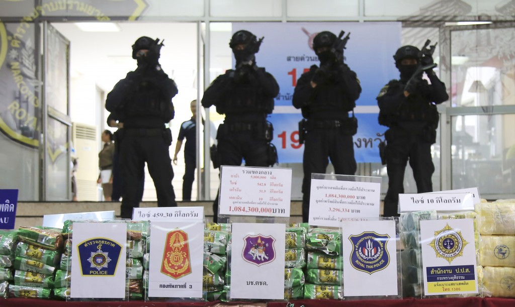 Thai policemen stand in front of packages of methamphetamines on display during a press conference at Narcotics Suppression Bureau Bangkok, Thailand,