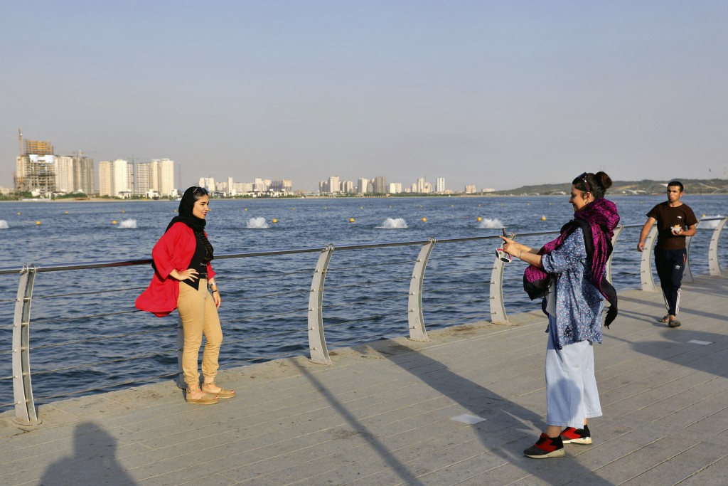 In this Saturday, July 6, 2019 photo, women take memorial picture while spending an afternoon around the Persian Gulf Martyrs' Lake in Tehran, Iran. A