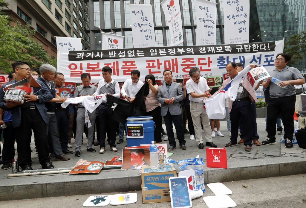 South Korean small and medium-sized business owners use scissors to cut t-shirts from Japanese brands during a rally calling for a boycott of Japanese...
