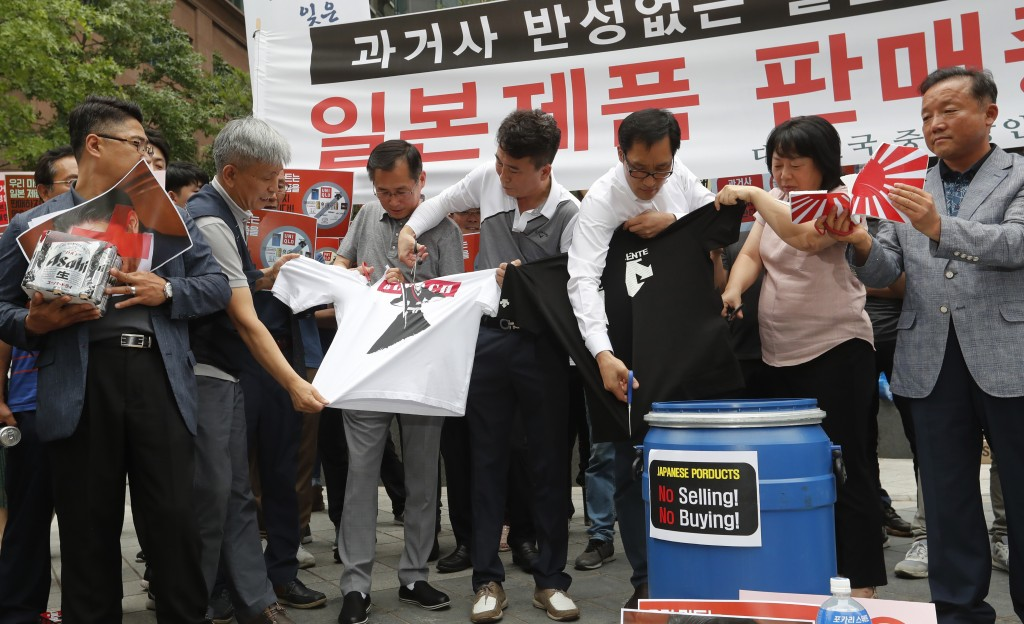 South Korean small and medium-sized business owners use scissors to cut t-shirts from Japanese brands during a rally calling for boycott of Japanese p...