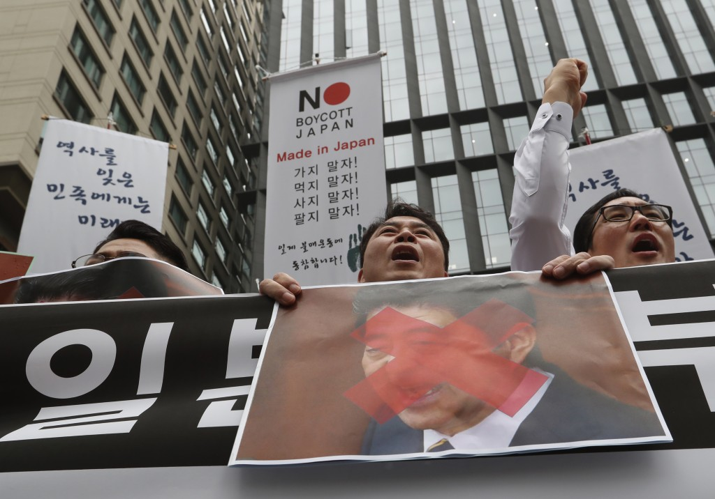 South Korean small and medium-sized business owners with a defaced image of Japanese Prime Minister Shinzo Abe shout slogans during a rally calling fo...