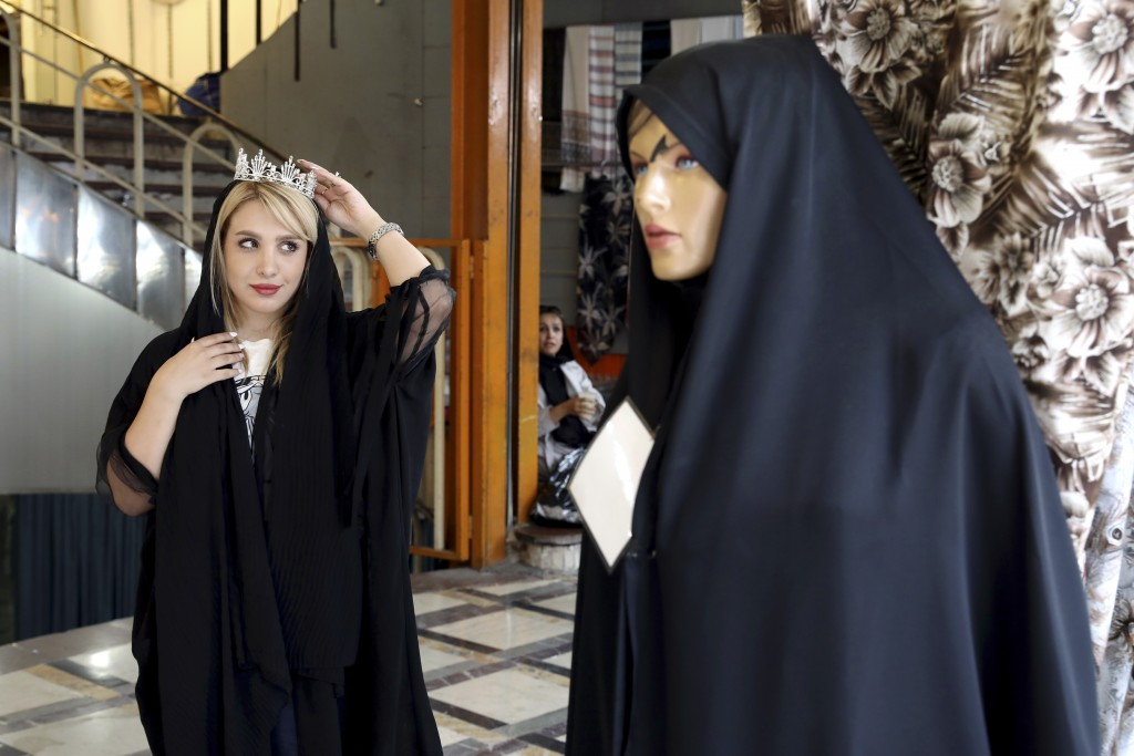 In this Wednesday, July 3, 2019 photo, a woman tests a crown for her wedding ceremony at a market in downtown Tehran, Iran.  A few daring women in Ira