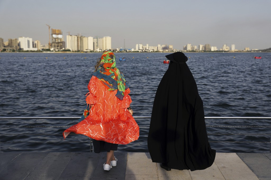 In this Saturday, July 6, 2019 photo, with different dress code, women spend an afternoon around the Persian Gulf Martyrs' Lake in Tehran, Iran. A few