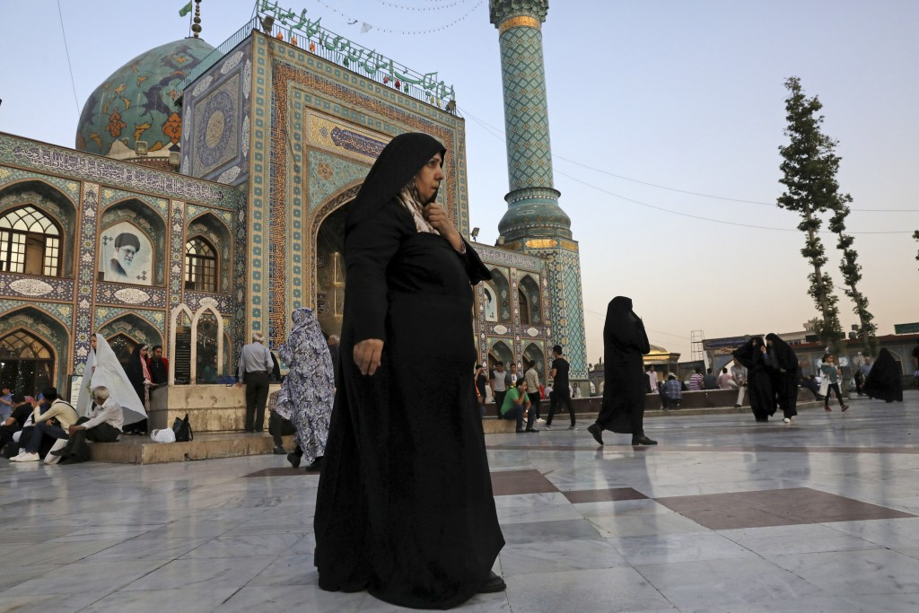 In this Tuesday, July 2, 2019 photo, a head-to-toe veiled woman walks in the courtyard of the shrine of Saint Saleh in northern Tehran, Iran.  A few d